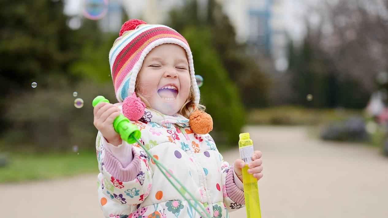 Barnallergifonden - Barn som blåser såpbubblor och skrattar